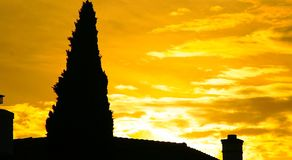 House of the Burning Sun. This is a picture of a home roof, two chimneys, and a large, protruding fir tree contrasted against the background of a bright setting Royalty Free Stock Images