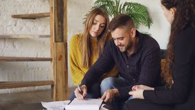 House buyer handsome man is signing sales agreement with housing agent, getting key and kissing his girlfriend after. House buyer handsome man is signing sales stock footage