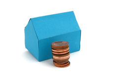 House buying. A blue paper house with some coins Royalty Free Stock Image