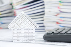House and calculator have blur pile of paperwork as background Stock Photography