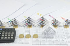 House with calculator between Pile of gold coins Royalty Free Stock Image