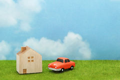 House and car on green grass over blue sky and clouds. My home and car concept Stock Photography