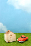House and car on green grass over blue sky and clouds. My home and car concept Royalty Free Stock Photography