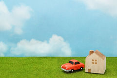 House and car on green grass over blue sky and clouds. My home and car concept Stock Photo