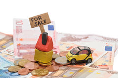 House and car for sale. Clay house and toy car for sale on pile of money on white background Royalty Free Stock Photos