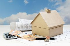 House from cardboard with money and calculator standing on archi royalty free stock photos