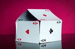 House of cards with aces on a red background. The idea of winning a cottage or a mansion