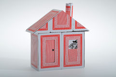 A house of cards. A flimsy house made from playing cards with a joker in the window with binoculars Royalty Free Stock Photo