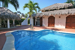 House in the Caribbean. Authentic house in the Caribbean style, with doors made of mahogany and teak furniture, palm gazebo, cool and clean swimming pool. What Stock Photography