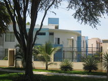 Suburban House. Located in a residential area in Piura, Peru. A carob tree is in front of the house stock images