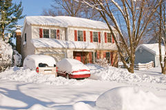 House and cars after snowstorm. Suburban house and front yard  with cars covered by drifted and blowing snow after a heavy winter snowstorm Royalty Free Stock Photo