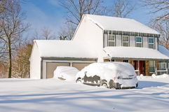 House and cars after snowstorm. Suburban house and front yard with cars covered by drifted and blowing snow after a heavy winter snowstorm Stock Photos