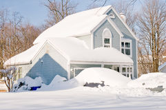 House and cars after snowstorm. Suburban house and front yard with cars covered by drifted and blowing snow after a heavy winter snowstorm Royalty Free Stock Images