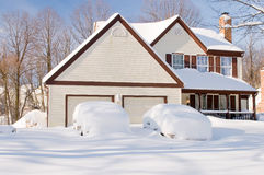 House and cars after snowstorm. Suburban house and front yard, snowbound, with cars covered by drifted and blowing snow after a heavy winter snowstorm Royalty Free Stock Image