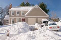 House and cars after snowstorm. Suburban house and front yard, snowbound, with cars covered by drifted and blowing snow after a heavy winter snowstorm Stock Image