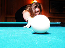 House champ. Woman out of focus shooting cue ball with focus on ball, shallow depth of field royalty free stock photos