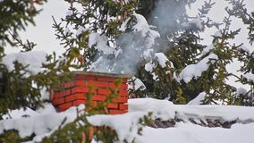 House chimney detail with smoke comming out of it among snow covered pine trees stock video