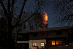 House Chimney Fire at Night with Burning Embers Falling to Roof stock photo