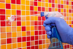 House chores - cleaning bathroom wall with sprayer. Person doing chores in bathroom at home cleaning tiled wall with spray detergent stock photo