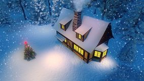 House and christmas tree at snowfall night top view. Cozy rustic house with smoking chimney and luminous windows and decorated Christmas tree at snowing night Stock Photography