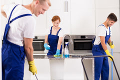 House cleaners cleaning kitchen. Team of professional house cleaners cleaning kitchen royalty free stock photo