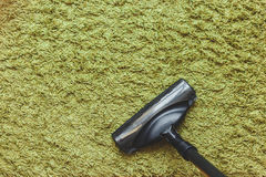House cleaning concept with space for text. The head of a vacuum cleaner brush on the green carpet, the top view. Royalty Free Stock Photography