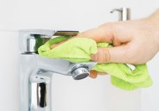 House cleaning. Man cleaning tap in bathroom stock image