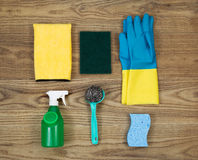 House Cleaning Materials on Age Wood. Overhead view of house cleaning materials placed on rustic wood.  Items include sponge, rubber gloves, stainless steel pad Stock Image