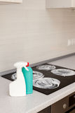 House cleaning - plastic bottles with detergents on kitchen tabletop on the background of electric stoves. Cleaning of induction s Royalty Free Stock Images