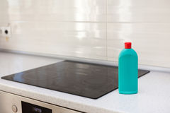 House cleaning - plastic bottles with detergents on kitchen tabletop. Washing of the hob. Induction stove. Electric stove. House cleaning - plastic bottles with Stock Images