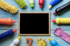 House cleaning product and blackboard. On wood table Stock Photography