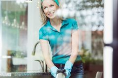 Cleaning kitchen furniture with cloth. House cleaning routine, happy middle-aged woman wearing blue rubber protective gloves cleaning kitchen furniture with stock images