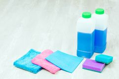 House cleaning supplies close up on wooden background. Rags and bottles. House cleaning supplies close up on wooden background Stock Images