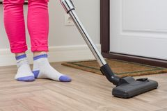 House cleaning. Woman is cleaning using vacuum cleaner royalty free stock photography