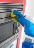 Woman is wiping microwave oven. Stock Photo