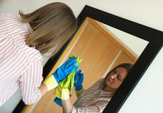 Woman is wiping mirror. House cleaning. Woman is wiping mirror in the room Royalty Free Stock Images