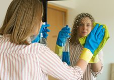 Woman is wiping mirror in the room. House cleaning. Woman is wiping mirror in the room Royalty Free Stock Photo