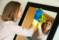 Woman is wiping mirror in the room. House cleaning. Woman is wiping mirror in the room Stock Image