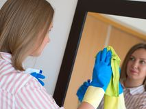 Woman is wiping mirror in the room. House cleaning. Woman is wiping mirror in the room Stock Images