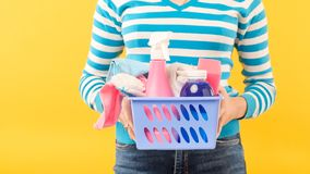 House cleanup cleaning set woman supplies basket. House cleanup. Basic cleaning set. Woman holding basket of supplies. Copy space on yellow background royalty free stock photo