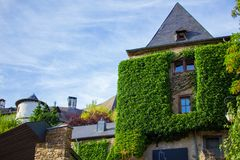 House with a climbing plant and the sky at the background in Clervaux, Luxembourg.  stock photography