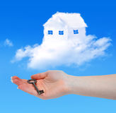 House from clouds. And hand with key Royalty Free Stock Photo