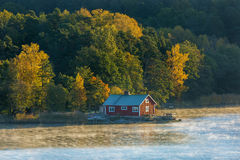 House on the coast with the autumn forest Royalty Free Stock Photo