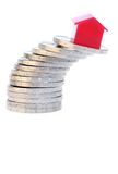 House on coins. A red house on a slanting stack of euro coins. Symbolizes uncertainty about the housing market Royalty Free Stock Image