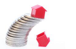 House on coins. A red house on a slanting stack of coins. Below one house that already fell. Symbolizes uncertainty about the real estate market Stock Photo