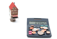 House with coins and calculator over white backgro Stock Image