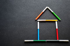 House of colored felt-tip pens. Stylized house out of colored felt-tip pens on a dark background Stock Photos