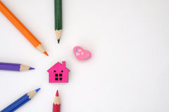 A house and colored pencils. A tiny house shape object and colored pencils arranged in patteren Royalty Free Stock Photos