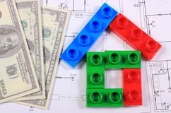 House of colorful building blocks and banknotes on drawing of home. House shape of colorful building blocks and banknotes lying on construction drawing of house Royalty Free Stock Photo