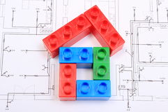 House of colorful building blocks on drawing of home. House shape of colorful plastic building blocks lying on construction drawing of house, concept of building royalty free stock image
